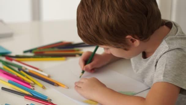 fiú ül az asztalnál, és a rajz