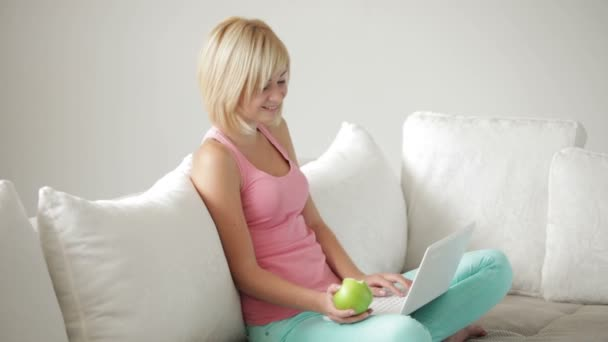 girl on couch eating apple using laptop