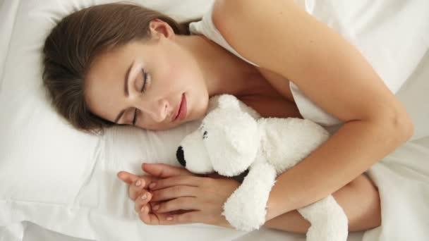 mladá žena spí v posteli