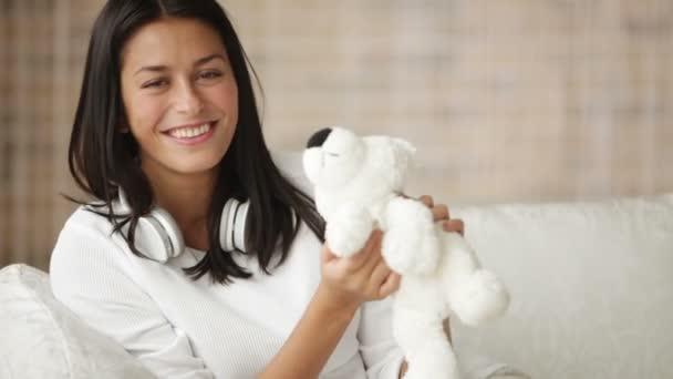 girl on sofa playing with teddy bear