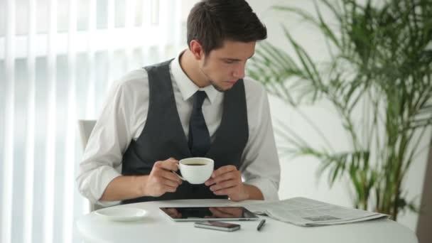 Mann sitzt am Tisch und liest Zeitung