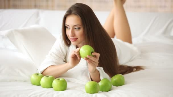 Beautiful girl lying on bed with apples