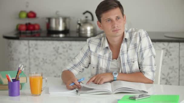 student studuje u kuchyňského stolu