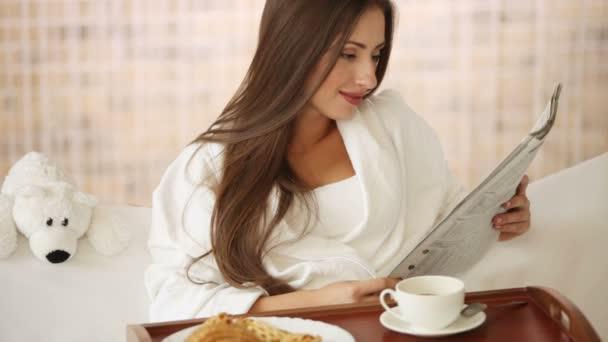 holka v posteli číst noviny