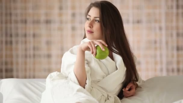 girl relaxing in bed playing with apple