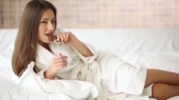 dívka ležela v posteli stravovací balíček čokolády