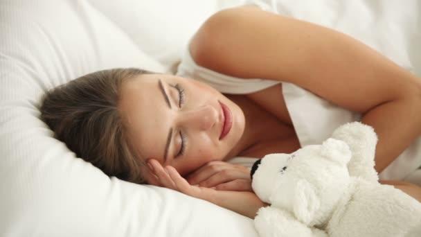 Vonzó fiatal nő alszik az ágyban mackó
