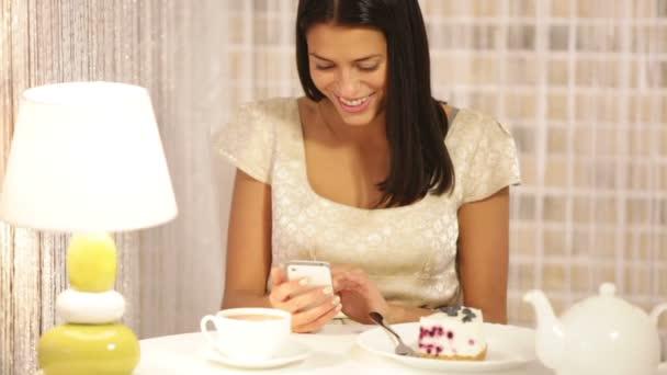 ragazza con tè e torta tramite cellulare