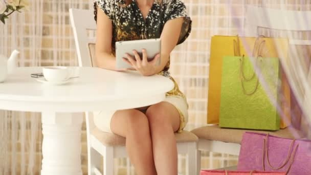 girl sitting at cafe with shopping bags