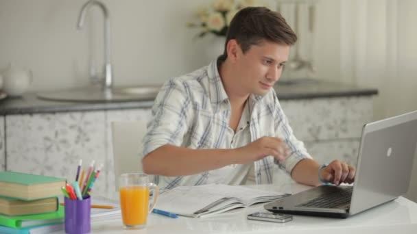 Student sedí u stolu studovat s notebookem