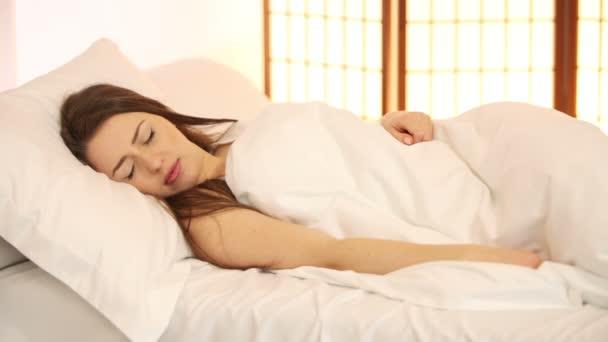 hezká mladá žena spí v posteli
