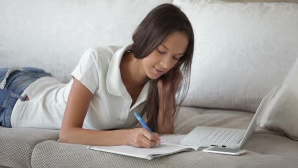 Dívka ležící na pohovce pomocí notebooku