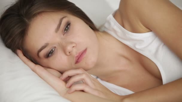 Attractive young woman lying in bed