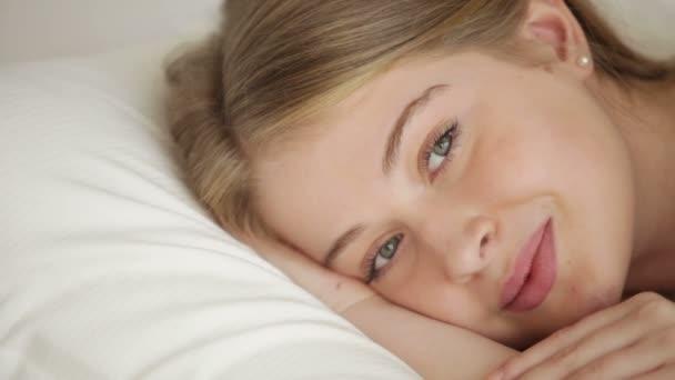 Krásná blondýnka, ležící v posteli