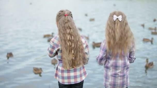 Two little girls feeding ducks