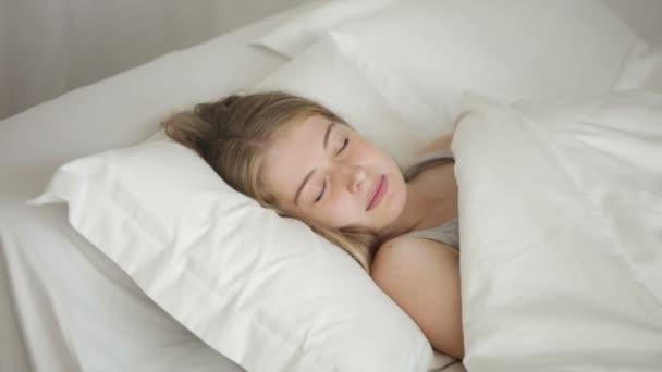 gyönyörű fiatal nő alszik az ágyban