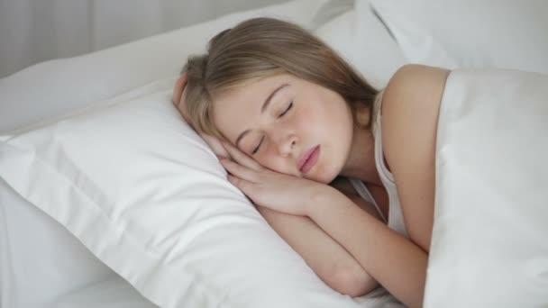roztomilá mladá žena spí v posteli
