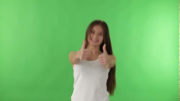 dívka na zeleném pozadí ukazuje palec