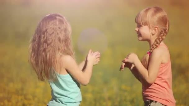 Dvě malé holčičky tleskat rukama v květech