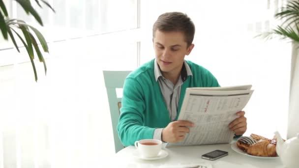 Muž, čtení novin, čaj