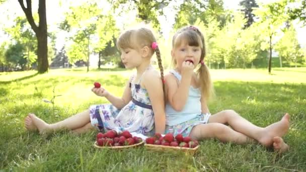 Happy kids eating  strawberries.