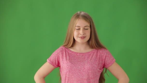 žena na zeleném pozadí ukazuje palec