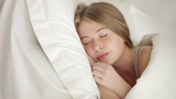 Szép szőke lány az ágyban alszik