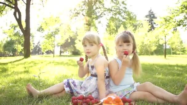 Happy kids eating  strawberries.