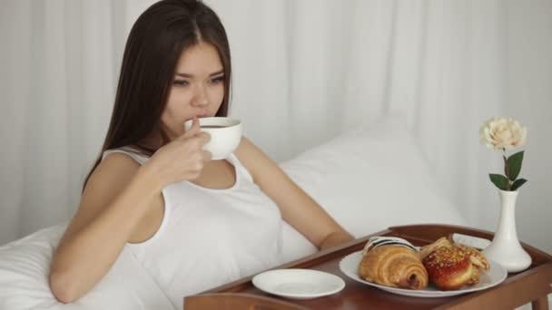 dívka sedící na posteli, pít z poháru