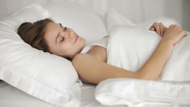 csinos, fiatal nő alszik az ágyban