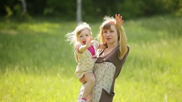 Happy mother and child waving  hands