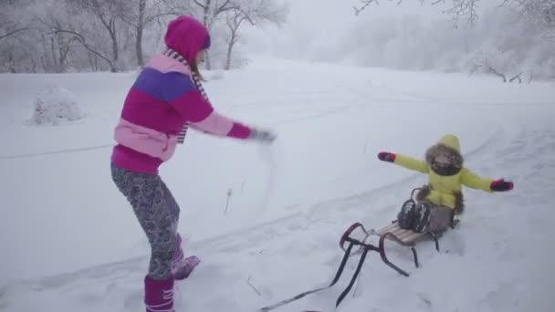 Mutter und Tochter werfen Schnee
