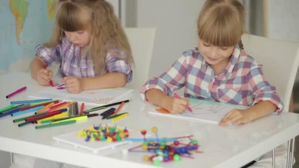 Két kislány rajz asztalnál ül