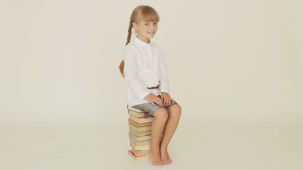 Roztomilá holčička sedí na hromadě knih