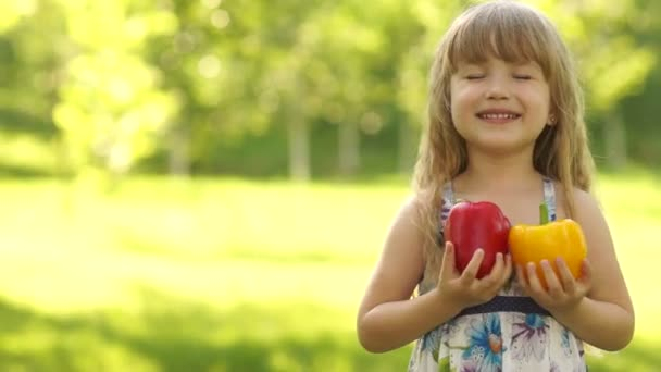 Child hugging two vegetable peppers