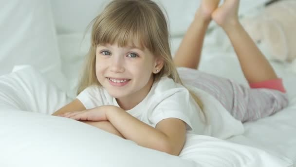 Funny little girl lying in bed