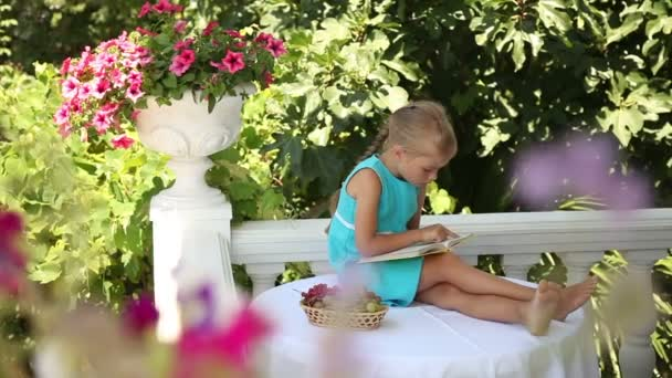 Happy little girl reading a yellow book