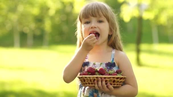 smiling child eating strawberries