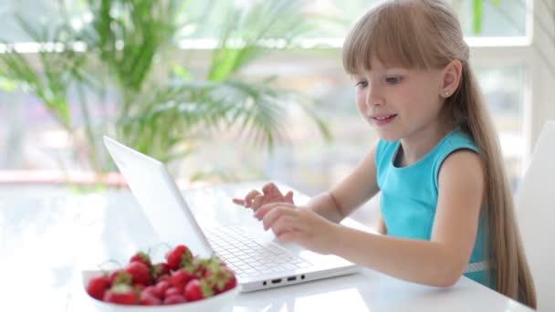 dívka sedí u stolu s notebookem