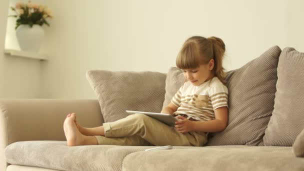 Girl with tablet sitting on sofa