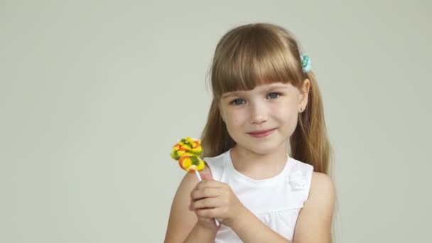 Little girl standing with a lollipop and smiling