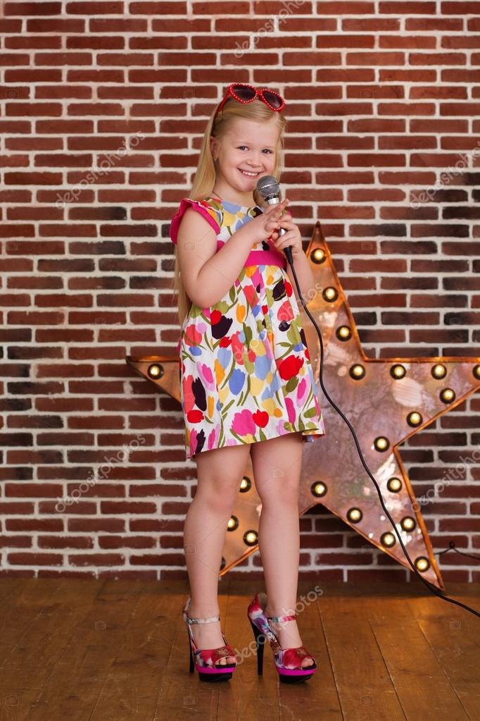 d3c079cc1d5e Beautiful little girl in dress and MOTHERS HEELS with microphone on brick  wall background — Photo by ...