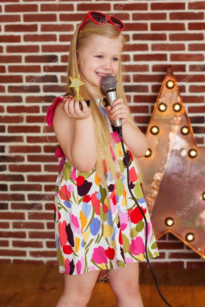 c688e1ac372f Beautiful little girl in fashion dress with microphone and reward statue in  hands on brick wall background — Photo by ...
