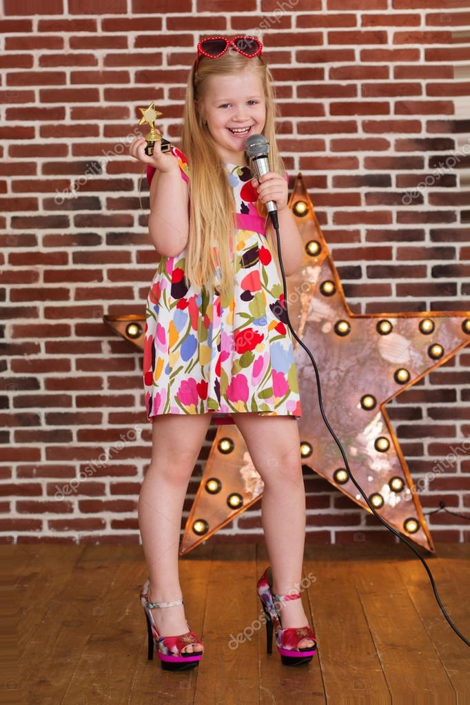 18e337a49f4a Beautiful little girl in fashion dress and MOTHERS HEELS with microphone on brick  wall background — Photo by ...