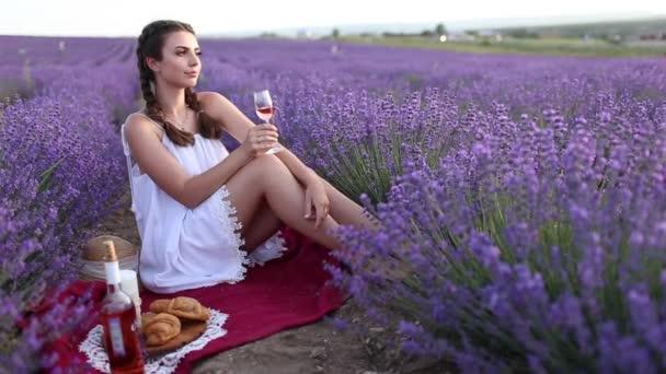 Portrét krásné dívky je na sobě velký klobouk s piknik a pití vína na levandulovém poli, Francie.