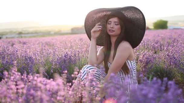 Portrét krásné dívky nosí velký klobouk sedí v levandulovém poli, Francie.