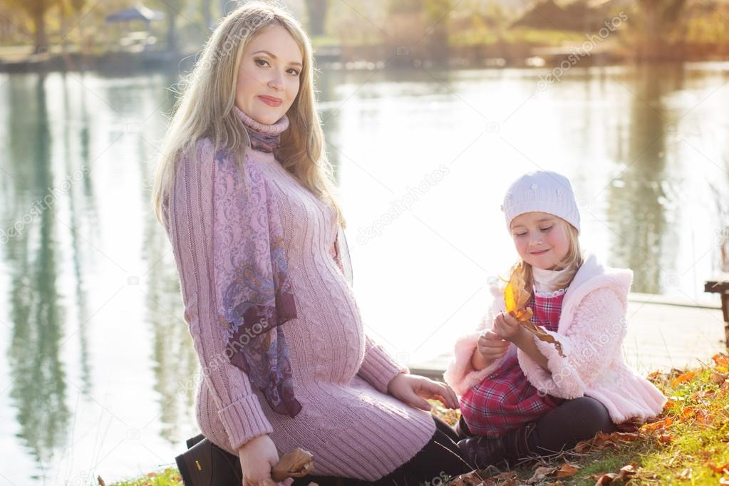 Little girl with her mother on the autumn lake