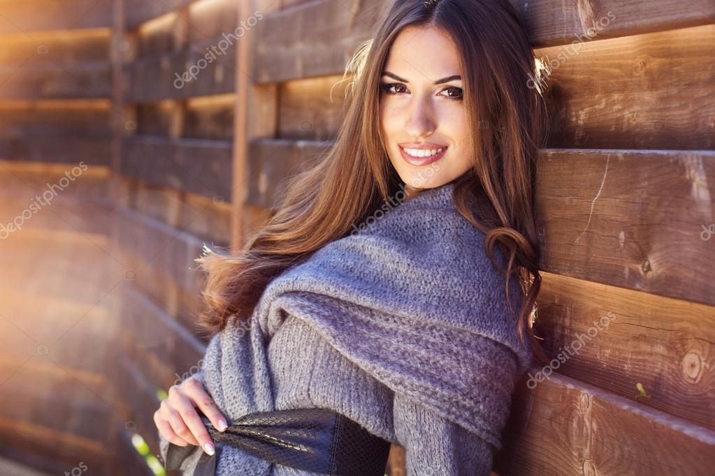 Young fashion girl near wooden wall