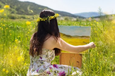 Pretty painter girl painting in yellow field