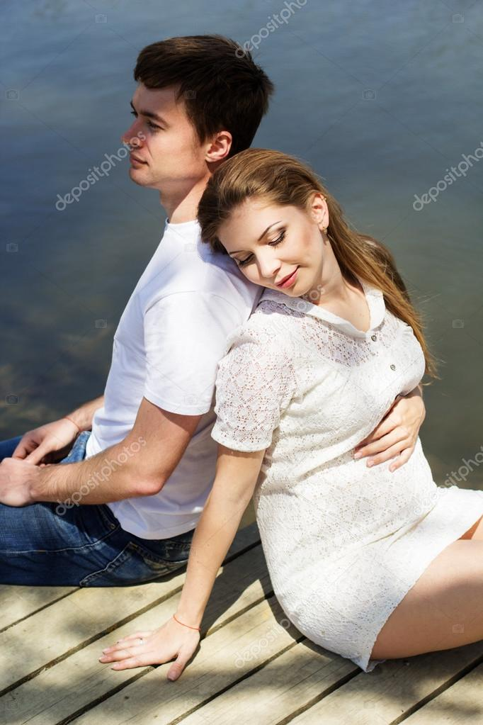 Pregnant girl with husband are sitting on bridge
